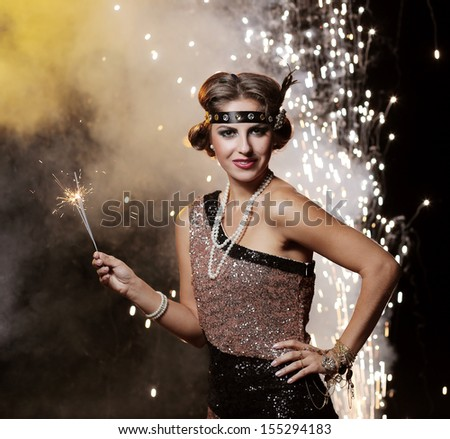 Portrait of a happy woman who is holding bengal lights over a sparkling background - stock photo