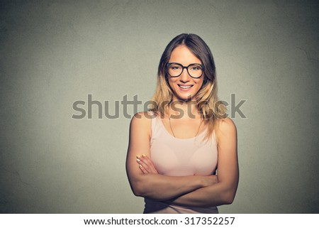 Portrait of a happy woman with arms folded and glasses standing over gray background. Looking at camera - stock photo