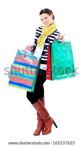 Portrait of a happy young adult girl, with color-coded bags. - stock photo
