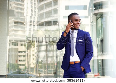 Portrait of a happy young african american businessman talking on cell phone while outdoors in the city - stock photo