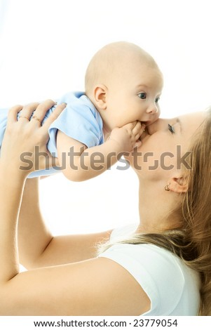 portrait of a happy young beautiful mother kissing her four months old baby - stock photo