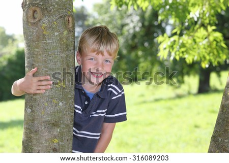 Portrait of a happy young boy outdoors - stock photo