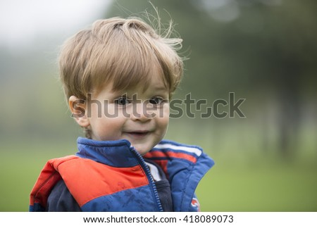 Portrait of a happy young boy outdoors.  - stock photo