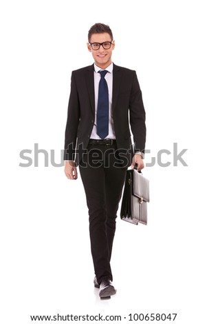 Portrait of a happy young business man carrying a suitcase, walking on white background - stock photo