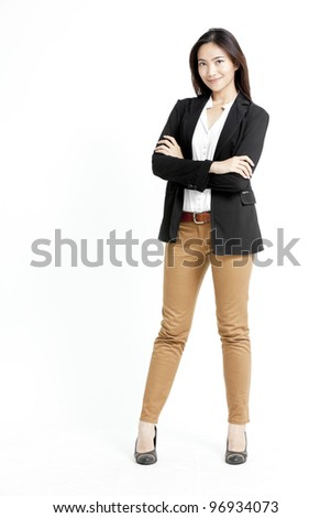Portrait of a happy young business woman standing with folded hand against white background - stock photo