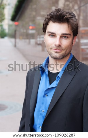 Portrait of a happy young businessman in suit standing outside office - stock photo