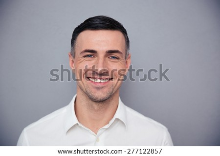 Portrait of a happy young businessman looking at camera over gray background - stock photo