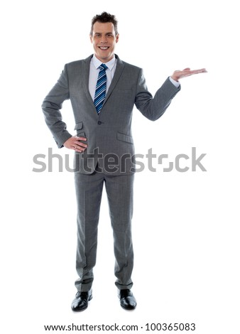 Portrait of a happy young businessman presenting a product against white background - copy space - stock photo