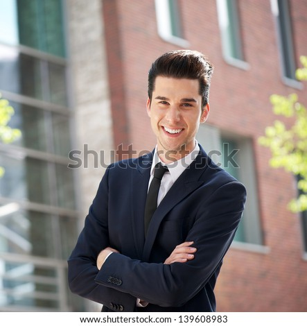 Portrait of a happy young businessman standing outside the office with arms crossed - stock photo