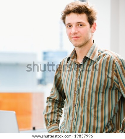 Portrait of a happy young casual businessman at office, smiling. - stock photo