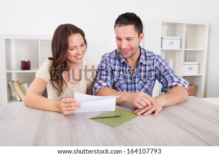 Portrait Of A Happy Young Couple At Home Reading Paper - stock photo