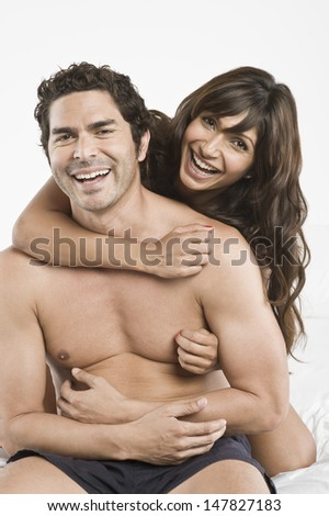 Portrait of a happy young couple being playful in bed - stock photo