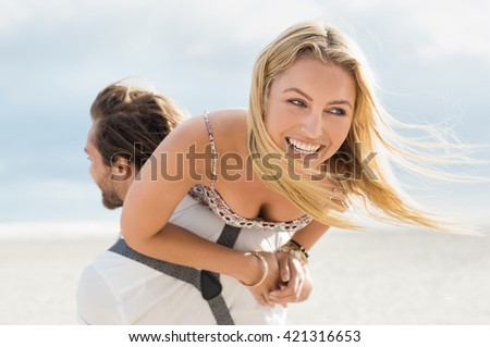 Portrait of a happy young couple enjoying outdoors. Cheerful man piggybacking woman at the beach. Young man giving his girlfriend on shoulder at sunset. 