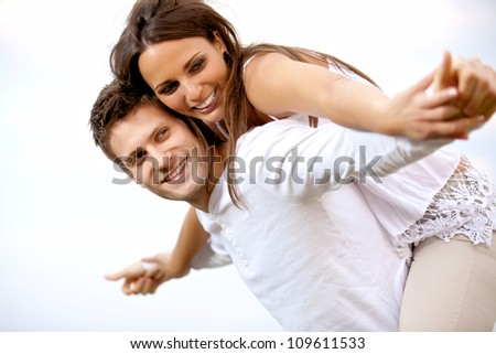 Portrait of a happy young couple having fun against a bright background - stock photo