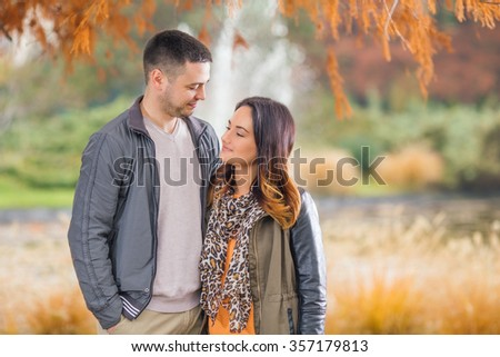 Portrait of a happy young couple looking at each other while walking through the park in autumn - stock photo