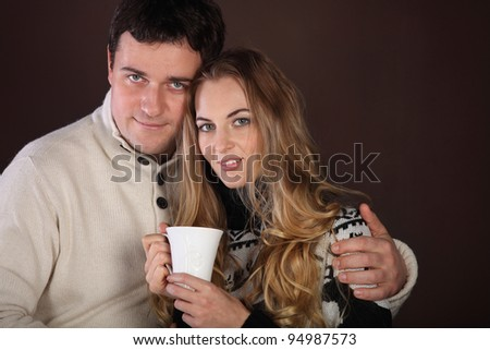 Portrait of a happy young couple over brown background. Copyspace - stock photo