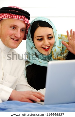 Portrait of a happy young couple sitting on a sofa using laptop - stock photo