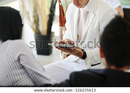 Portrait of a happy young couple talking to financial advisor at home - stock photo