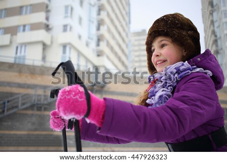 Portrait of a happy young girl in a winter hat with ski poles near the blocks of flats - stock photo