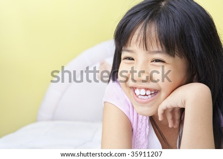 portrait of a happy young girl in bedroom - stock photo