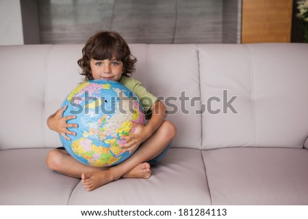 Portrait of a happy young kid with globe sitting in the living room at home - stock photo