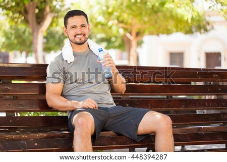 Portrait of a happy young man drinking some water from a bottle while sitting and resting in a park bench after doing some jogging outdoors - stock photo