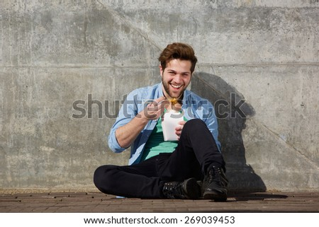 Portrait of a happy young man eating asian food with chopsticks  - stock photo