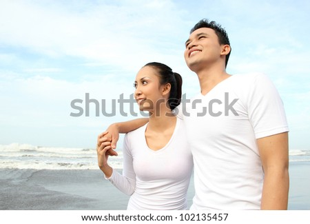 Portrait of a happy young man hugging his girlfriend at the beach - stock photo