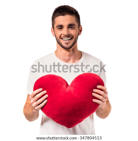 Portrait of a happy young man in love with heart in hand isolated on a white background - stock photo