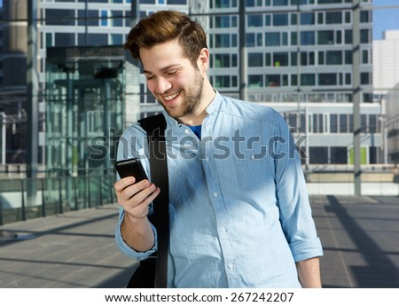 Portrait of a happy young man sending text message from mobile phone at the airport - stock photo