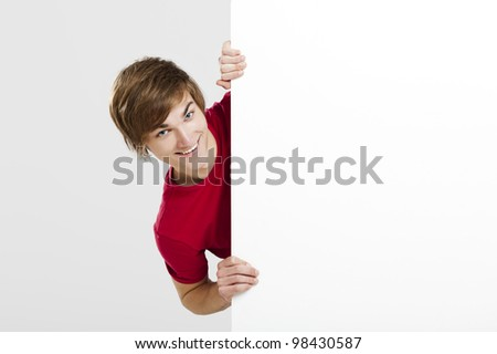 Portrait of a happy young man showing something on a blank white card - stock photo