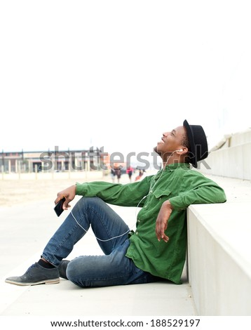 Portrait of a happy young man sitting outdoors listening to music on mobile phone - stock photo