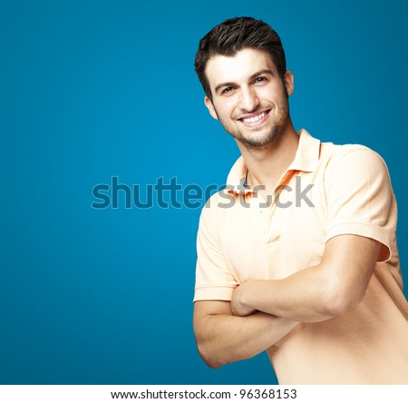 portrait of a happy young man smiling against a blue background - stock photo