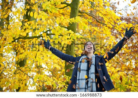 Portrait of a happy young man smiling and throwing leaves with open arms - stock photo