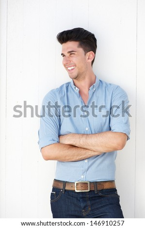 Portrait of a happy young man standing against white wall outdoors - stock photo