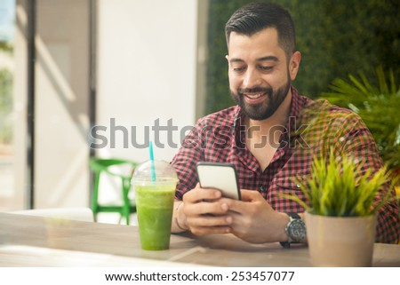 Portrait of a happy young man using a smartphone while drinking a healthy smoothie - stock photo
