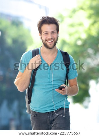 Portrait of a happy young man walking outdoors with cellphone  - stock photo
