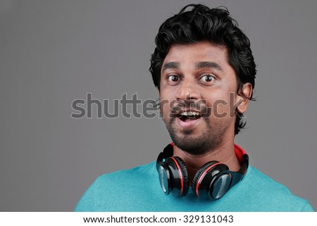 Portrait of a happy young man with a headphone on his neck - stock photo