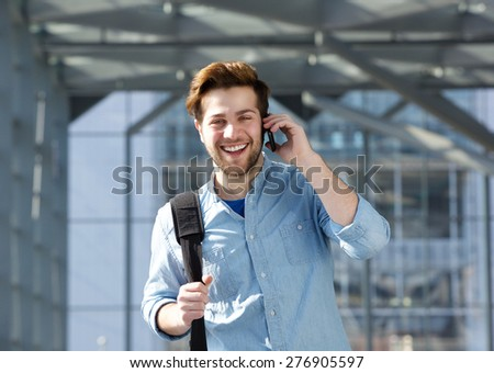 Portrait of a happy young man with bag talking on cell phone - stock photo