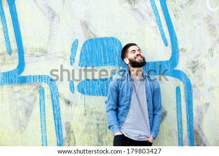 Portrait of a happy young man with beard smiling and listening to music on earphones outdoors - stock photo