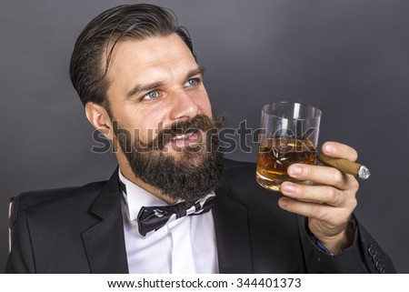 Portrait of a happy young man with retro look sitting in an armchair,smoking and holding a glass of whiskey over gray background - stock photo