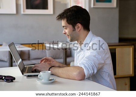 Portrait of a happy young man working on laptop  - stock photo