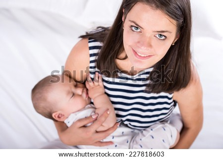 Portrait of a happy young mother is holding a sleeping baby. - stock photo