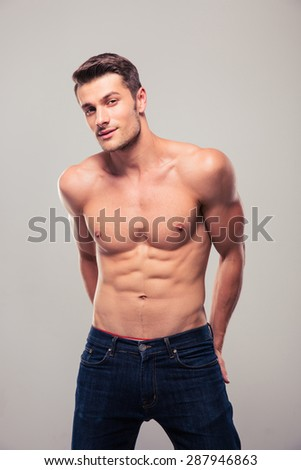 Portrait of a happy young muscular man posing over gray background. Looking at camera - stock photo