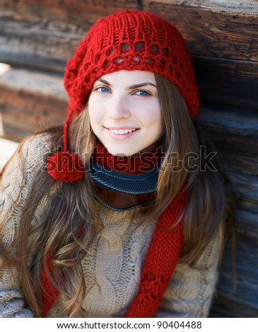Portrait of a happy young woman against wooden wall with ski mask and red hat. - stock photo