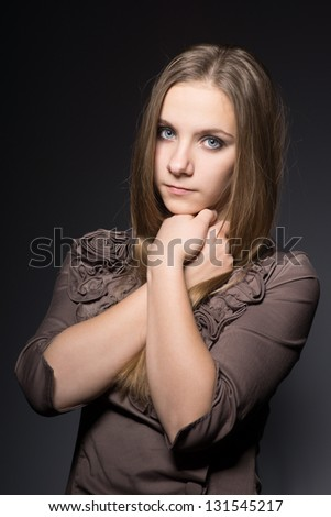 Portrait of a happy young woman. Close-up. Hand near her chin. On a gray background - stock photo