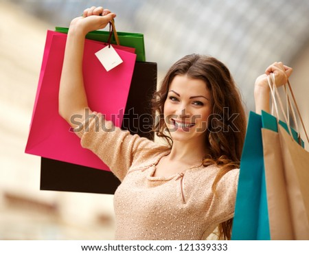 Portrait of a happy young woman holding shopping bags at the mall - stock photo