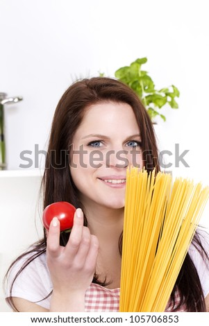portrait of a happy young woman holding spaghetti and tomato - stock photo