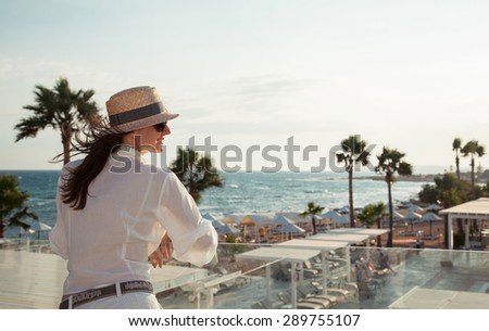 Portrait of a happy  young woman in a hat near the sea - stock photo