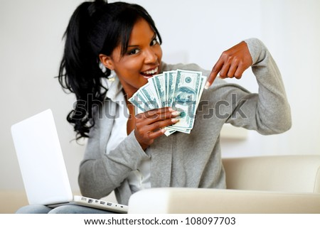 Portrait of a happy young woman pointing plenty of cash money - stock photo